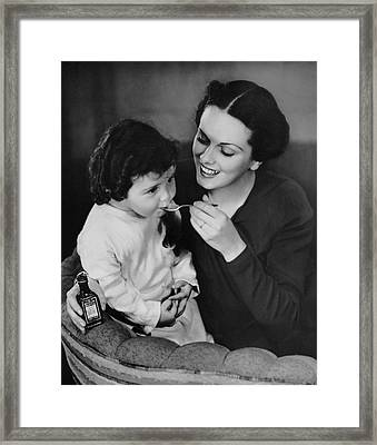 Mother Giving Spoon Of Medicine To Child Framed Print by George Marks