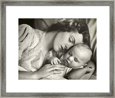 Mother Holding Infant In Bed Framed Print by George Marks