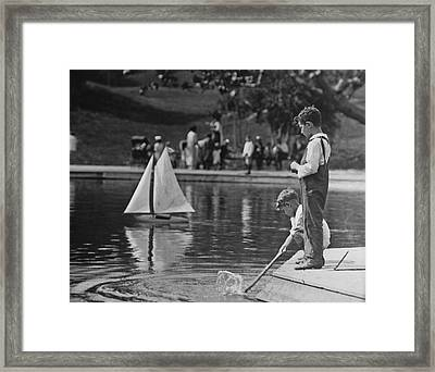 Playing With A Model Boat Framed Print by Fpg