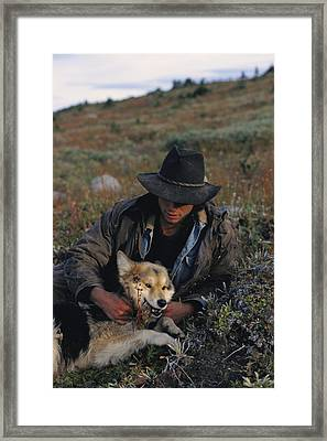 Portrait Of A Wrangler With His Pet Dog Framed Print by Raymond Gehman