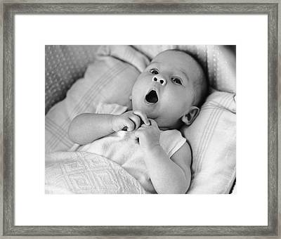 Portrait Of Baby Yawning Under Blankets Framed Print by George Marks
