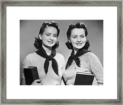 Portrait Of Teenaged Twin Girls Holding Books Framed Print by George Marks