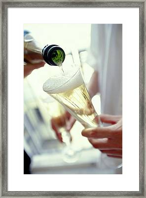 Pouring Champagne Framed Print by David Munns