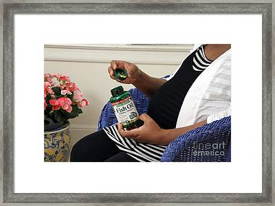 Pregnant Woman Taking Fish Oil Framed Print by Photo Researchers