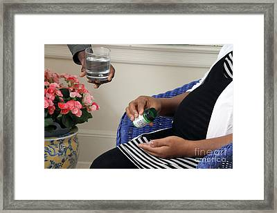 Pregnant Woman Taking Folic Acid Framed Print by Photo Researchers