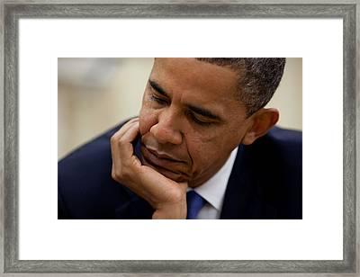 President Barack Obama Reads A Document Framed Print by Everett