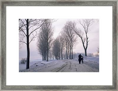 Pushing A Bike Along A Snow Covered Framed Print by Gordon Wiltsie