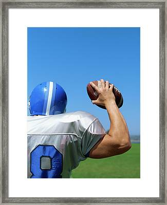 Rear View Of A Football Player Throwing A Football Framed Print by Stockbyte