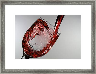 Red Wine Splashing From A Glass Cup Framed Print by Paul Ge