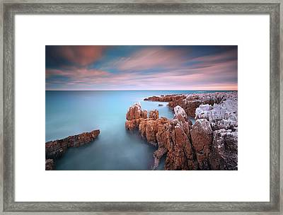 Rocks In Sea At Sunset Framed Print by Eric Rousset