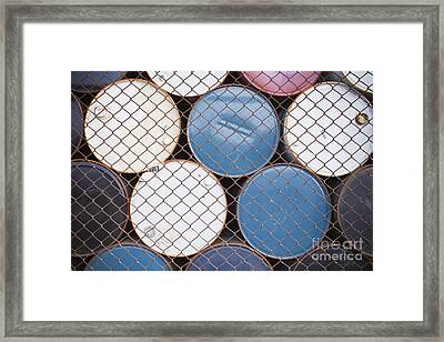 Rows Of Stacked Barrels Behind A Fence Framed Print by Paul Edmondson