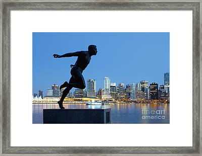 Running Sculpture With A Downtown Background Framed Print