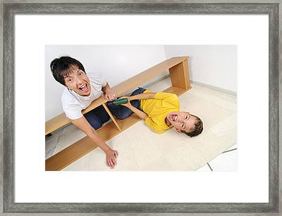 Screaming Mother And Son Assembling Furniture Framed Print by Matthias Hauser