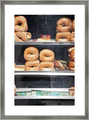 Selection Of Bagels On Shelves Behind A Shop Window Framed Print by Paul Hudson