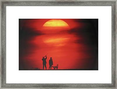 Silhouette Of Couple With Dog, Man Aiming, Sunset Framed Print by David De Lossy