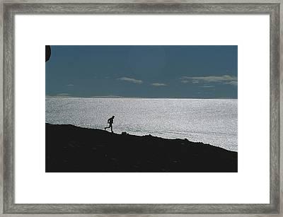 Silhouette Of Man Jogging Past A Bare Framed Print by Gordon Wiltsie