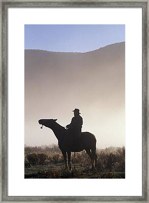 Silhouetted Cowboy On Horseback In Fog Framed Print