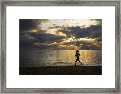 Silhouetted Woman Jogging On A Beach Framed Print by Mattias Klum