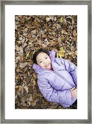 Smiling Girl Lying On Autumn Leaves Framed Print by Ian Boddy