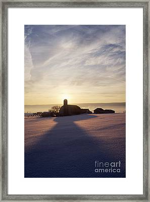 Snow Covered Field With Farm Silhouette At Sunset Framed Print by Jeremy Woodhouse
