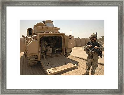 Soldiers Climb Into The Back Of A M2 Framed Print by Stocktrek Images