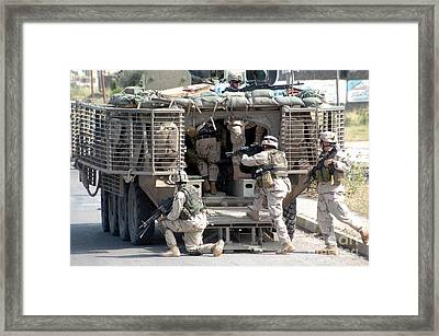 Soldiers Load In To The Stryker Armored Framed Print by Stocktrek Images