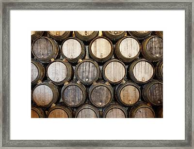 Stacked Oak Barrels In A Winery Framed Print by Marc Volk