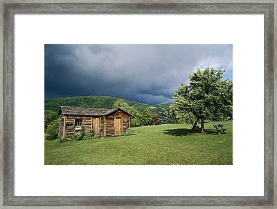 Storm Clouds Form Above A Log Cabin Framed Print by Raymond Gehman