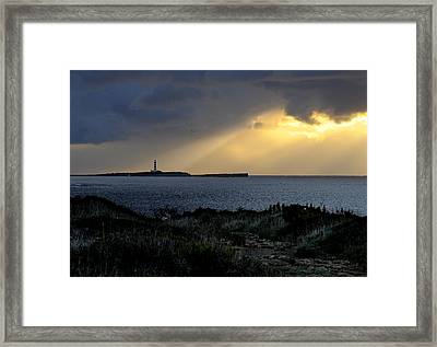 storm light - A morning light iluminates lighthouse through clouds in an amazing landscape Framed Print by Pedro Cardona