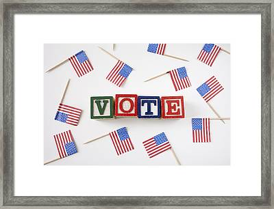 Studio Shot Of Small American Flags And Wooden Blocks With Text Vote Framed Print by Winslow Productions