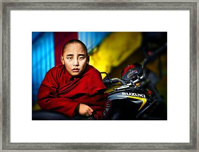 The Boy Monk In Red Robe Standing Beside A Motorcycle In A Buddh Framed Print by Max Drukpa