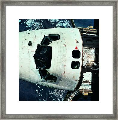 The Space Shuttle Orbiting Above The Earth Framed Print by Stockbyte