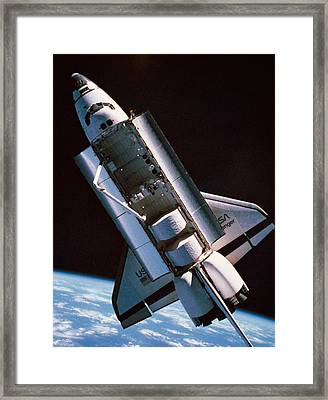 The Space Shuttle With Cargo Bay Open Orbiting Above Earth Framed Print