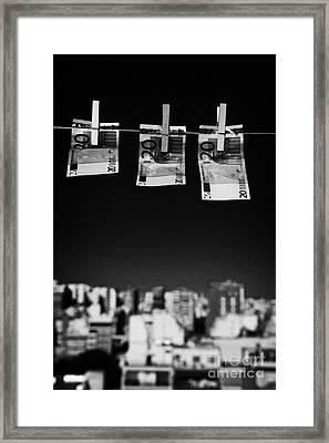 Three Twenty Euro Banknotes Hanging On A Washing Line With Blue Sky Over City Skyline Framed Print by Joe Fox
