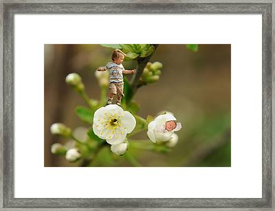 Two Tiny Kids Playing On Flowers Framed Print by Jaroslaw Grudzinski