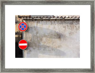 Two Traffic Signs On A Wall In The Town Framed Print