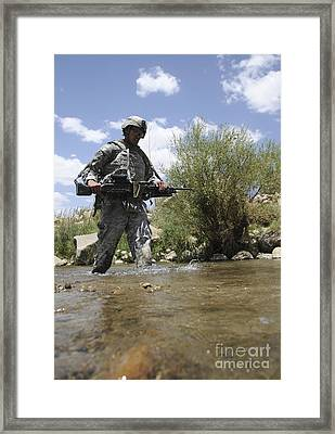 U.s. Army Soldier Crosses A Stream Framed Print