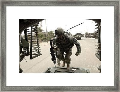 U.s. Army Specialist Entering A Stryker Framed Print
