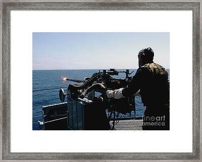U.s. Navy Gunners Mate Fires A Mark 38 Framed Print by Stocktrek Images