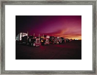 Vivid Sunset Over Trucks Parked Framed Print by Scott Sroka