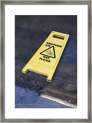 Wet Floor Sign In Puddle Framed Print by Mark Williamson