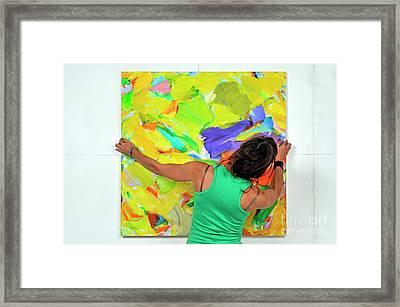 Woman Adjusting A Painting Framed Print by Sami Sarkis