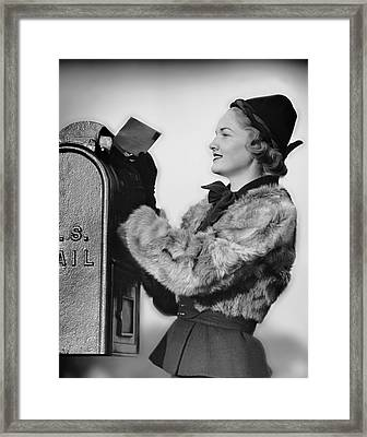 Woman Dropping Letter Into Mailbox Framed Print by George Marks
