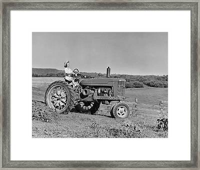 Woman Farmer Driving Tractor Framed Print by George Marks
