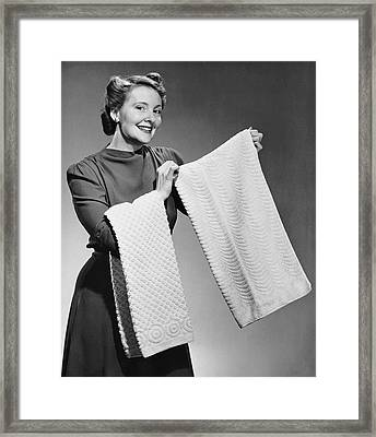 Woman Holding Up Towels Framed Print by George Marks