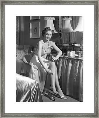 Woman In Bedroom Putting On Lotion Framed Print by George Marks