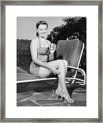 Woman On Lawn Chair Applying Oil To Her Legs Framed Print by George Marks