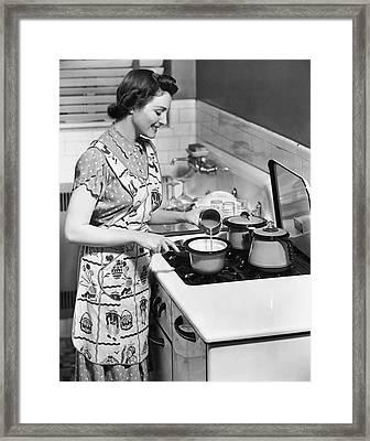Woman Preparing Food On Stove Framed Print by George Marks