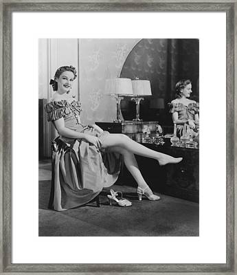 Woman Sitting At Vanity Table, Putting On Stockings, (b&w), Portrait Framed Print by George Marks