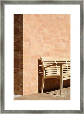 Wooden Bench Against Corner Of Brick Building Framed Print by Jeremy Woodhouse